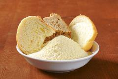 Pieces of stale bread and pile of finely ground bread crumbs - stock photo