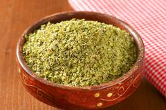 Heap of dried Marjoram leaves in a wooden bowl - stock photo