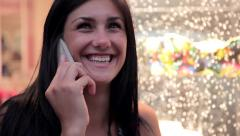 Woman laughing on the phone in front of dress shop closeup Stock Footage
