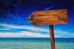 Stock Photo of Direction Signpost on Seaside Beach
