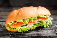 Sandwich with salmon patty and vegetables - stock photo