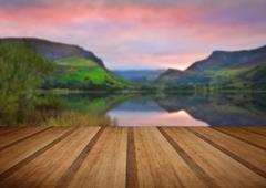 View of Snowdon covered in cloud at sunrise from Llyn Nantlle with wooden pla - stock photo