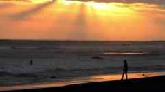 Woman Walks On Beach with Inspirational Sunbeams in The Background 4K Stock Footage