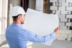 Cheerful young builder is studying the layout of new project Stock Photos
