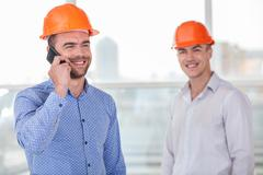 Young team of builders received approval for building - stock photo