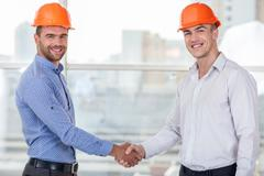 Stock Photo of Attractive young workers is congratulating each other