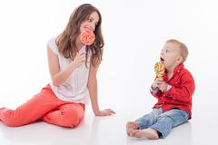 Cheerful young woman is treating her child - stock photo