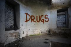 text drugs on the dirty old wall in an abandoned ruined house - stock photo