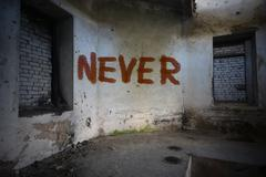 text never on the dirty old wall in an abandoned ruined house - stock photo
