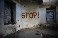 text stop on the dirty old wall in an abandoned ruined house - stock photo