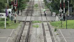 Telephoto shot into distance of woman and traffic crossing railway line. Stock Footage