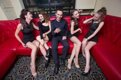 sexy lovelace man surrounded by hot women wanting of proposal from him - stock photo