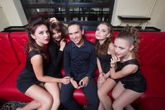 Sexy lovelace man surrounded by hot women wanting of proposal from him Stock Photos