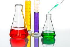 science Laboratory glassware pipette drop, reflective white background - stock photo