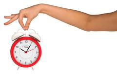 Hand holding alarm clock - stock photo