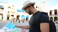 Tourist consulting a city guide searching locations in Havana, Cuba Stock Footage