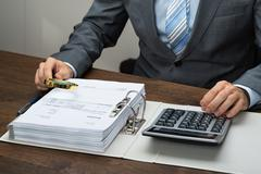 Close-up Of Businessman Inspecting Receipts With Magnifying Glass In Office - stock photo