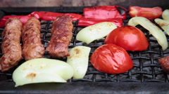 Sausages and vegetables on grill outdoors at barbecue Stock Footage