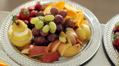Sliced pear, orange, apple, strawberries and grapes lying on a large platter Stock Footage