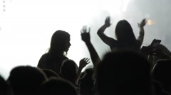 Crowd at the concert / Silhouettes of two dancing girls - stock footage