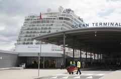 Cruise ship alongside Ocean terminal and porter with luggage Southampton UK - stock photo