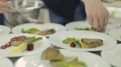 Chef spread foie gras on plates and pours with berry sauce Stock Footage