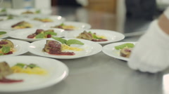 Chef spread foie gras on plates, pouring berry sauce and waiters take away Stock Footage