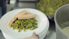 Stock Video Footage of Chef puts on a plate braised green beans and salmon and pouring sauce with red