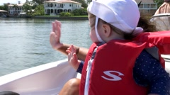 Cute litte girl waves to houses as she passes on boat, 4K Stock Footage