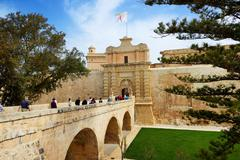 SLIEMA, MALTA - APRIL 19: The entrance in Medival Mdina town and tourists on - stock photo