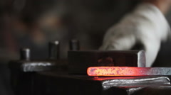 Forging hot metal in smithy - stock footage