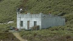 Panning down scene looking to an abandoned house, Alisa Craig, Scotland Stock Footage