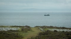 Small fishing boat passes the Ailsa Craig, Scotland Stock Footage