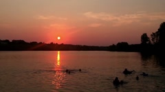 People bathe in the lake at sunset. Stock Footage