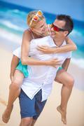 Happy young couple enjoying a solitary beach backriding - stock photo