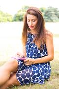 young woman writting on a notepad in the park - stock photo