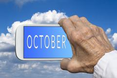 Stock Photo of Smart phone in old hand with month of the year - October on screen.
