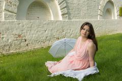 Romantic girl in a light pink tunic in a park Stock Photos