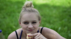 Girl eating wafer-cake and looking to the camera Stock Footage