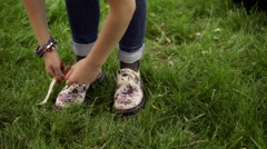 Girl standing on the grass and tying shoe laces Stock Footage