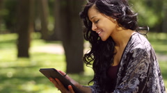 Young woman using an ipad/tablet in a park, close up - stock footage