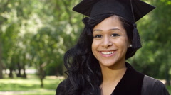 Outdoor portrait of a young woman graduate - stock footage