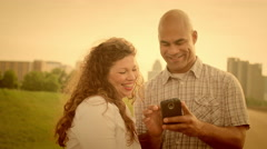 Warmly-tinted happy couple using a smart phone in Detroit 4K - stock footage