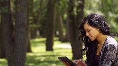 Young woman using an ipad/tablet in an outdoor park (pan shot) - stock footage