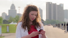Brunette woman using a smart phone in Detroit 4K - stock footage