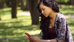 A young woman texting in outdoor park (pan down shot) - stock footage