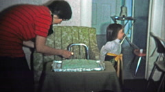 BOULDER, CO. USA - 1974: Mom lights birthday cake and fashionable girl sits at Stock Footage