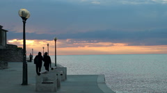 People Walking by the sea at Sunset Stock Footage