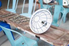 blurry defocused image of blue metal chair with old wooden door panel and lam - stock photo
