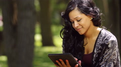 A young woman using her ipad outdoors in a park close up Stock Footage